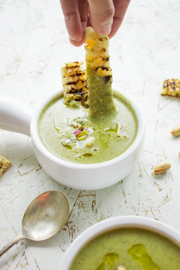 a toasted breadstick being dipped into a bowl of Smooth Blue Cheese Broccoli Soup.