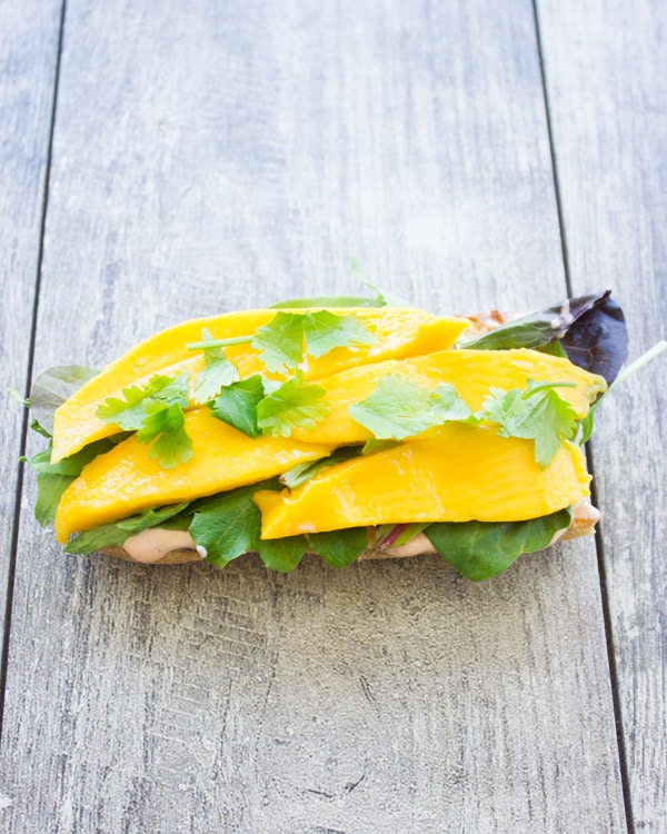 half a ciabatta bun topped with mango slices and cilantro