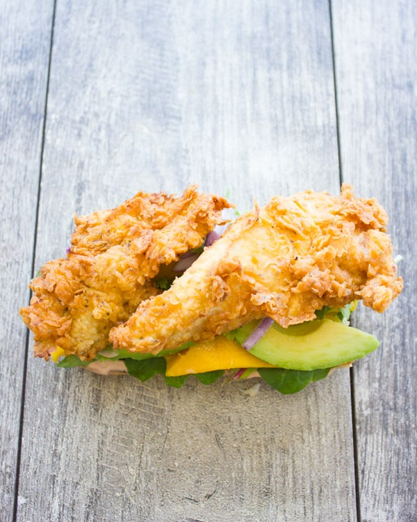 open ciabatta sandwich topped with crispy fried chicken, mango and avocado slices