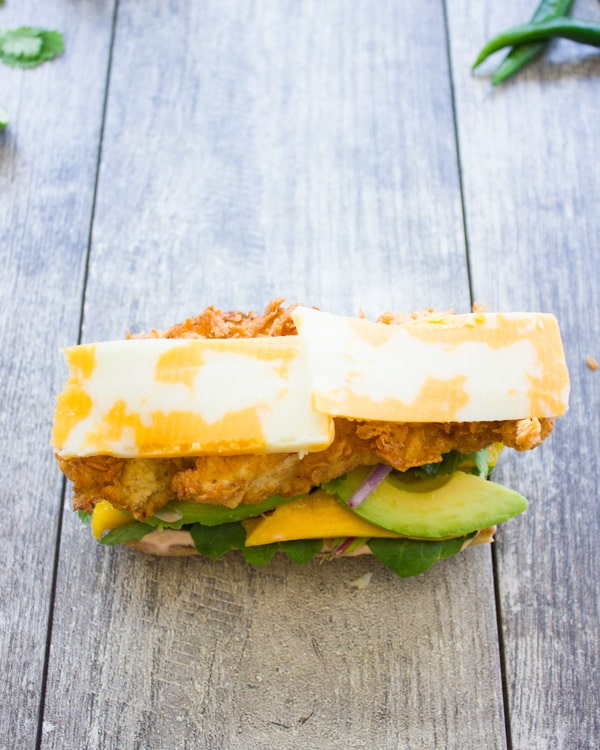 an open sandwich topped with fried chicken fingers, mango and marbled cheddar cheese