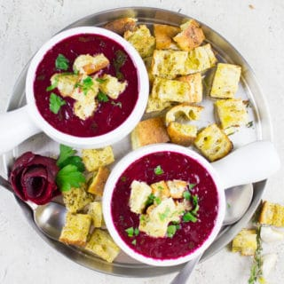 overhead shot of two bowls of Russian Beetroot Soup with croutons