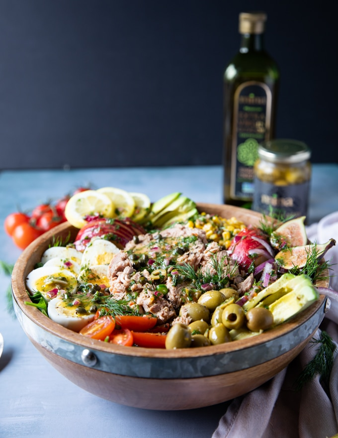 A huge bowl of tuna salad surrounded by a tea towel, a bottle of mina olive oil, some tomatoes on the board and a fork and spoon to serve