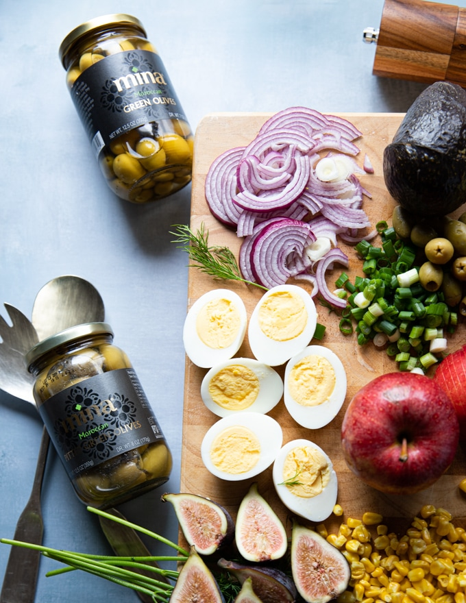 bottled green olives from Morocco on a board next to the hard boiled eggs, sliced onions, jalapenos, ready to go in to the salad