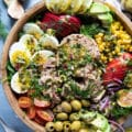 close up of a tuna salad recipe in a wooden bowl showing large chinks of tuna, boiled egs, olives, corn, avocados, tomatoes, apples, spinach and fresh herbs