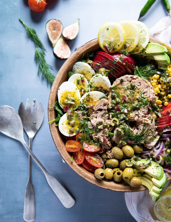 half plate of tuna salad recipe with a serving set of spoons and fork on a blue board. Fresh dill and tomatoes surrounding the big bowl of tuna salad. Salad includes chunky tuna, hard boiled eggs, apples, tomatoes, avocados, olives, lemon slices