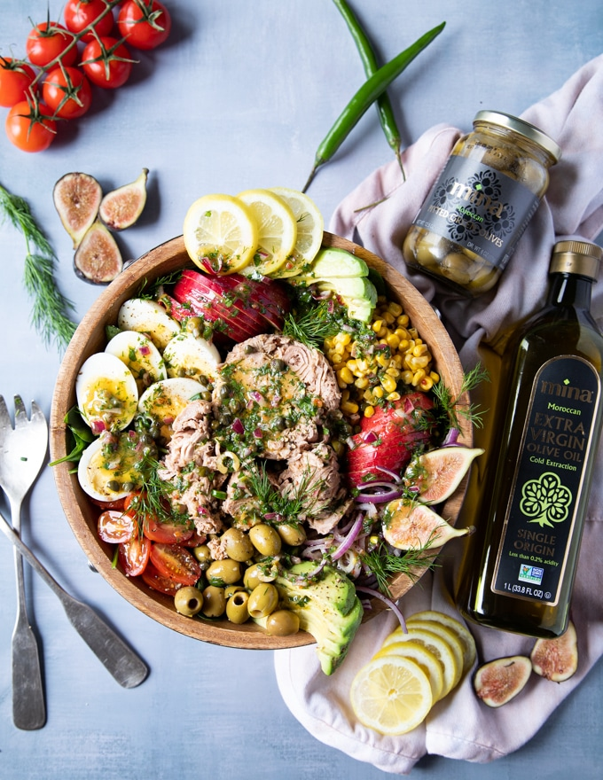 finished tuna salad recipe with the bottle of olive oil and green olives on the side. Some fresh figs on the table, a serving spoon and fresh dill. The tuna salad recipe is loaded with tuna, hard boiled eggs, avocados, tomatoes, apples, corn and tomatoes