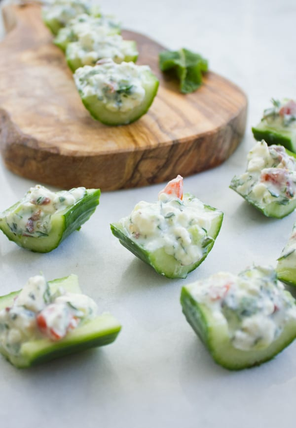Cucumber Salad Bites filled with herbs, feta cheese and tomatoes arranged on a wooden chopping board