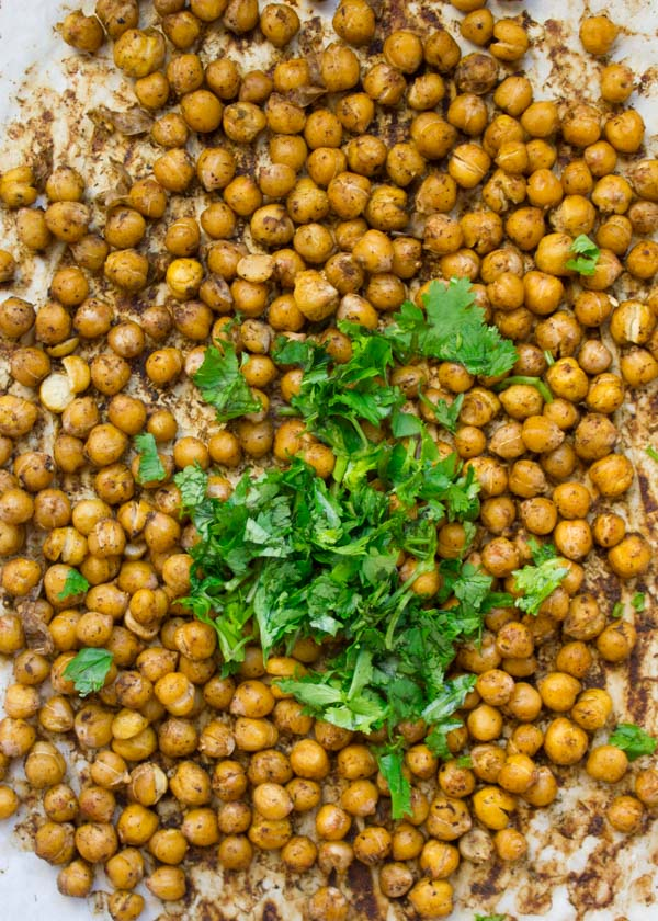 seasoned canned chickpeas on a parchment paper lined tray ready to be roasted
