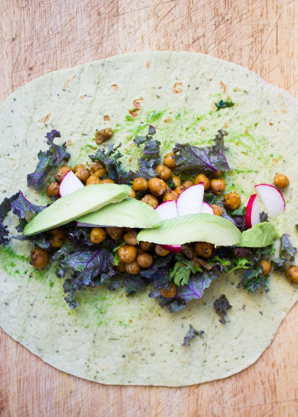 wheat tortilla being filled with roasted chickpeas avocado and veggies to make wraps