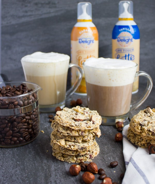 Coffee Bean Crunch Italian Cookies stacked in front of 2 cups of cappuccino and a jar with coffee beans