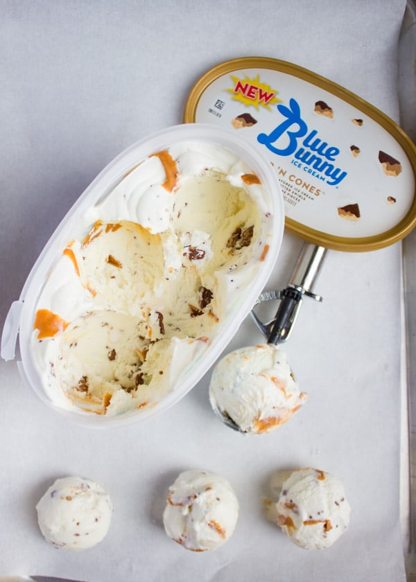 Some ice cream scooped over a parchment paper and the box of ice cream opened with the scoop.
