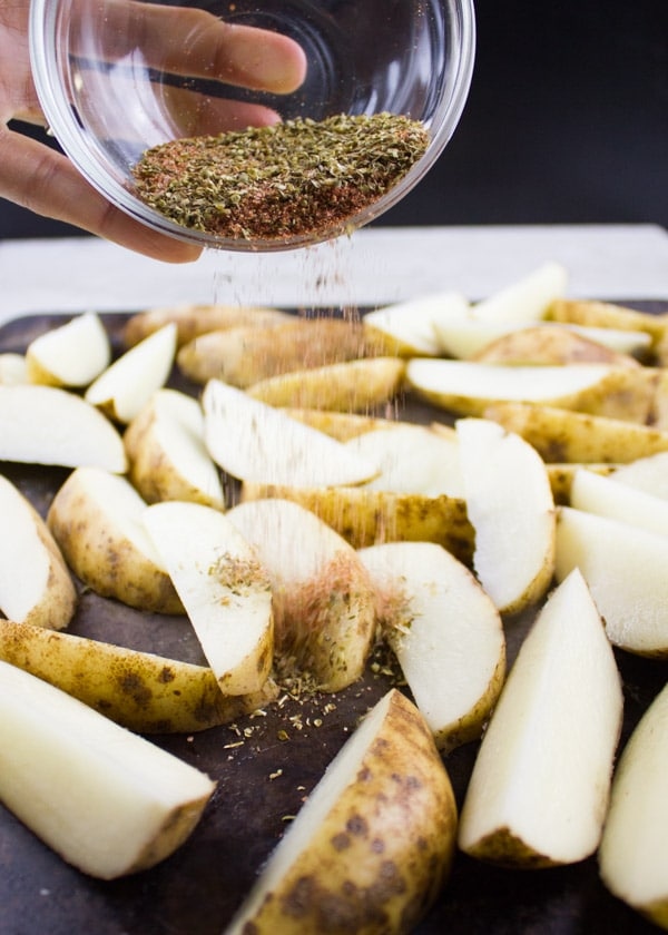 a spice mix being sprinkled on top of unbaked potato wedges