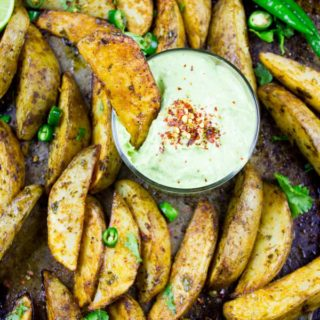 Perfect Baked Potato Wedges with Avocado Crema. Upgrade your average potatoes with these crispy spicy perfect baked potato wedges! Cool them off with a dip in the most luscious avocado sauce! Step by Step recipe at www.twopurplefigs.com