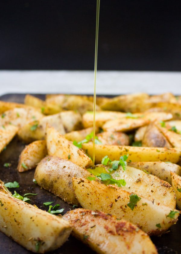Potato Wedges being drizzled with olive oil before baking