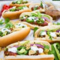 Grilled Hot Dogs Loaded with Nachos Toppings. Your Hot Dog BBQ is about to get AMAZING! Succulent hot dogs, Salsa, avocados, onions, and crispy chips! Step by step recipe at www.twopurplefigs.com