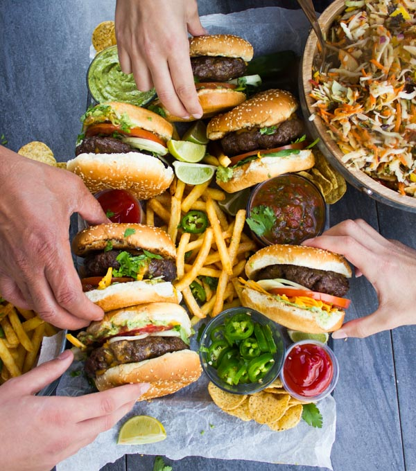 Overhead shot of 4 hands reaching for Lamb Burgers Loaded with Nacho toppings on a plate with french fries, jalapeno slices and guacamole.