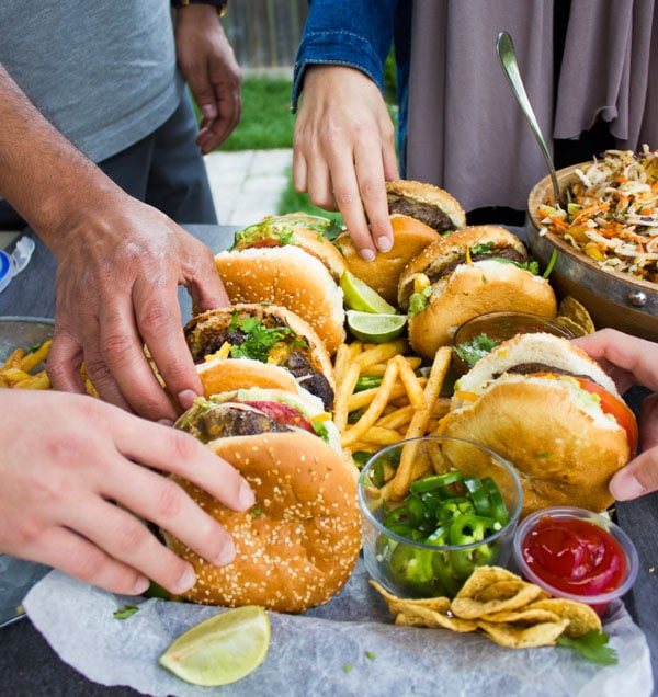 hand reaching for lamb burgers arranged on a pile of french fries with little side dishes with ketchup and guacamole nestles in between the fries.