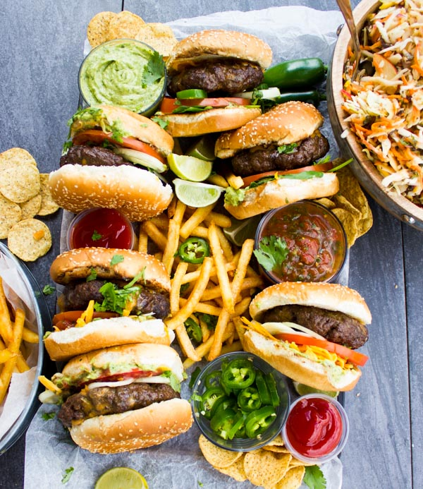 Overhead shot of Lamb Burgers Loaded with Nacho toppings on a plate with french fries and little glass bowl filled with jalapeno slices and guacamole.