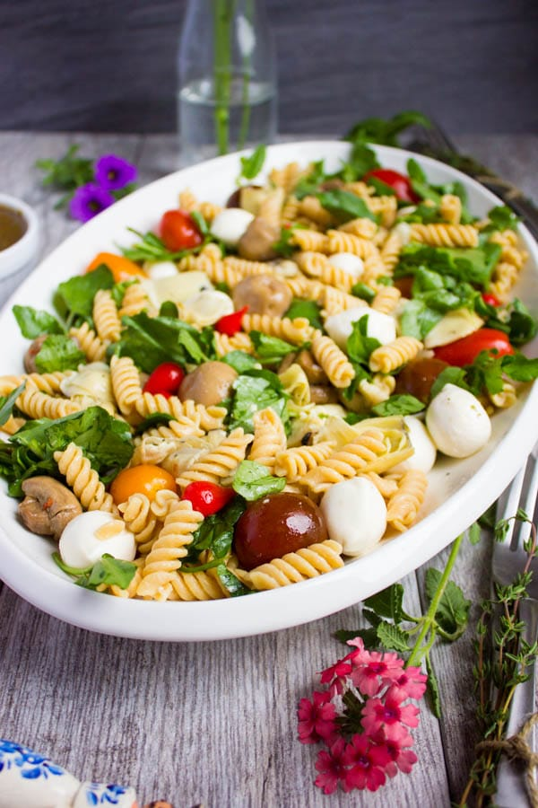 side view of Warm Antipasto Platter Pasta with basil sauce and mozzarella on a rustic table