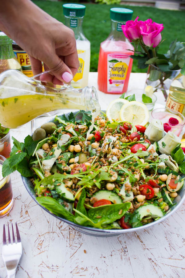 Zesty Lemonade Dressing being poured on top of a bowl of Mediterranean Farro Salad placed on a table outside.