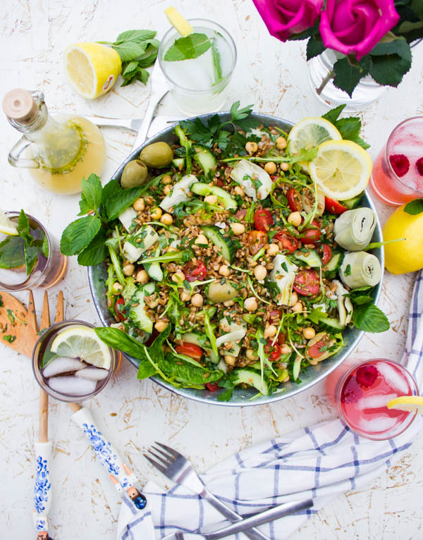 Overhead shot of a bowl of Mediterranean Farro Salad with some glasses of lemonade and wooden salad spoons surrounding it.