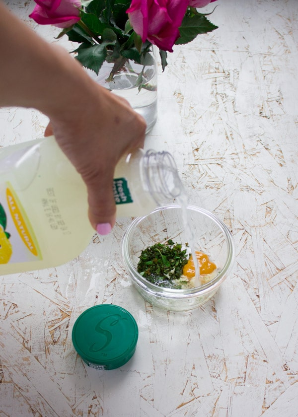lemonade being poured into a glass bowl with spices and herbs to make a salad dressing.