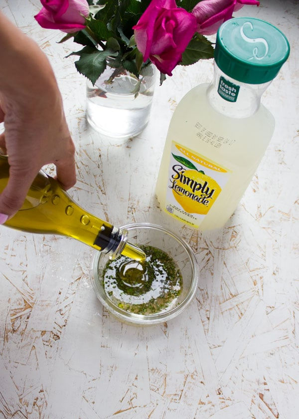 olive oil being drizzled into a glass bowl with lemonade dressing.