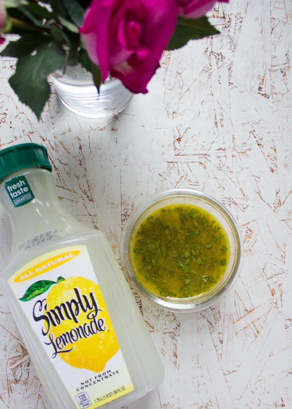 Sweet Zesty Lemonade Dressing in a small glass bowl next to a bottle of lemonade.