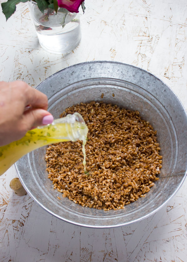 Sweet Zesty Lemonade Dressing being poured on top of a bowl with farro.