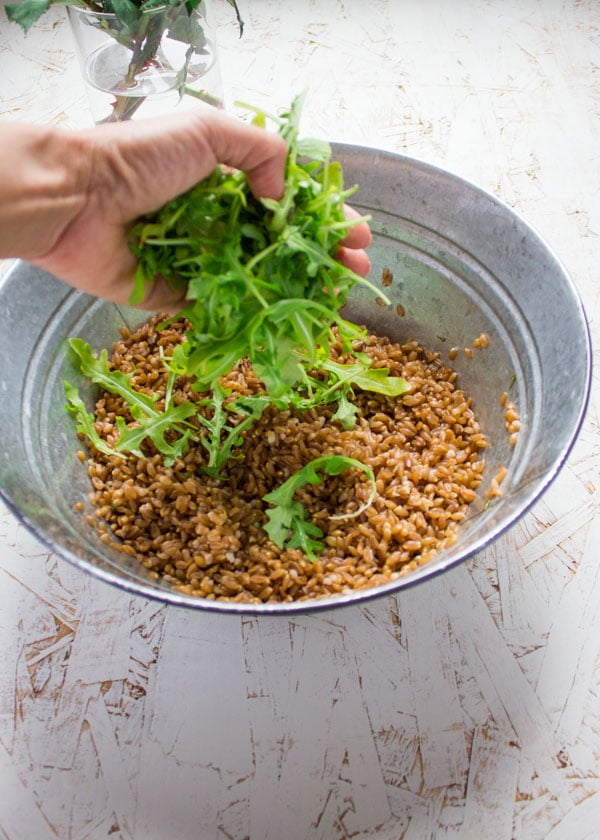 a hand full of arugula being added to a glass bowl with farro.