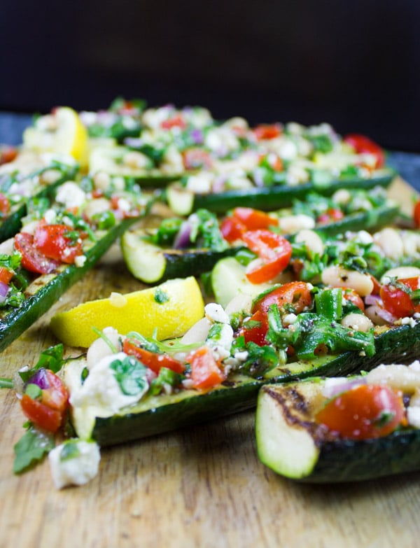 Zucchini Boats Grilled & Loaded With White Bean Salad. Even zucchini haters will love this--because it's all about the zesty bright Mediterranean filling! Easy, fresh, simple and utterly delicious way to use zucchini! Recipe at www.twopurpelfigs.com