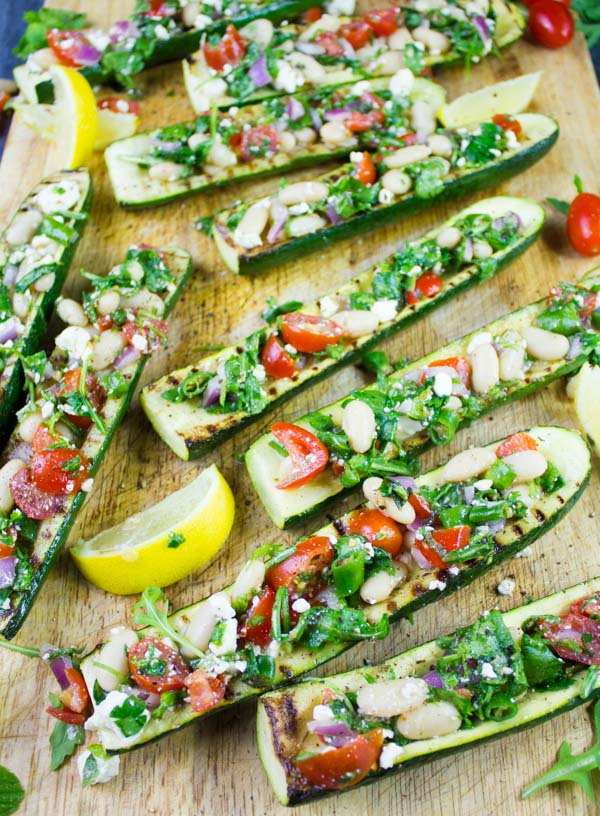 Overhead shot of grilled Zucchini Boats loaded with White Bean Salad served on a wooden chopping board with some lemon slices on the side.