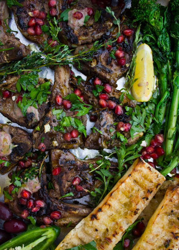 Succulent Grilled Lamb Chops with Black Olive Herb Butter sprinkled with pomegranate seeds and arranged on a silver platter with grilled rapini as well as some charred garlic baguette.