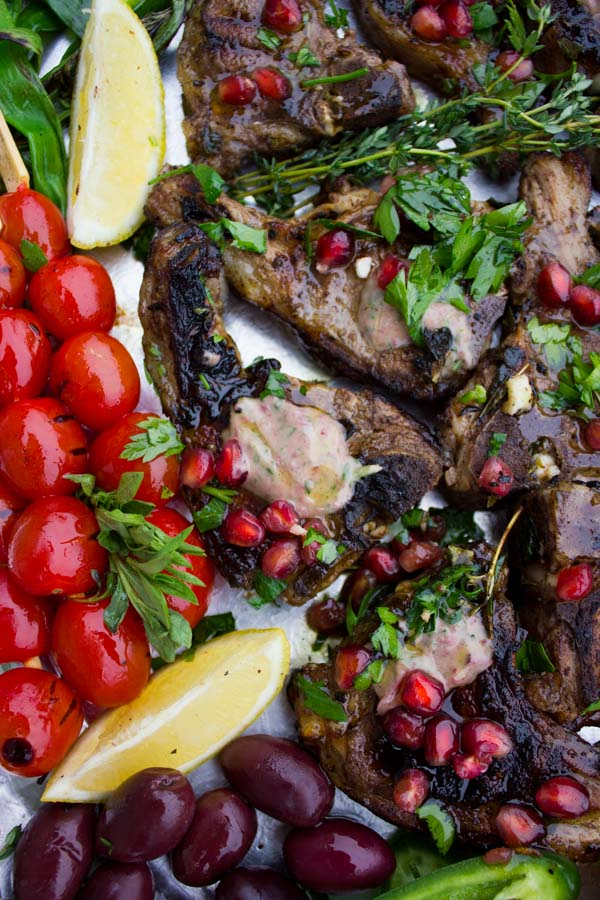 Succulent Grilled Lamb Chops with Black Olive Herb Butter sprinkled with pomegranate seeds and arranged on a silver platter with blistered cocktail tomatoes and fresh herbs