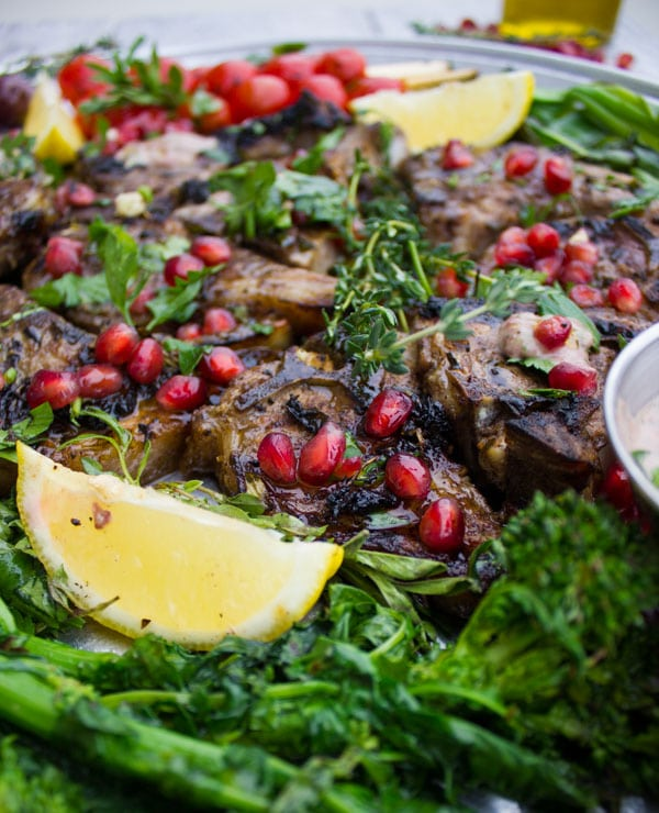 Close-up of Succulent Grilled Lamb Chops with Black Olive Herb Butter sprinkled with pomegranate seeds and arranged on a silver platter with blistered cocktail tomatoes and grilled rapini.