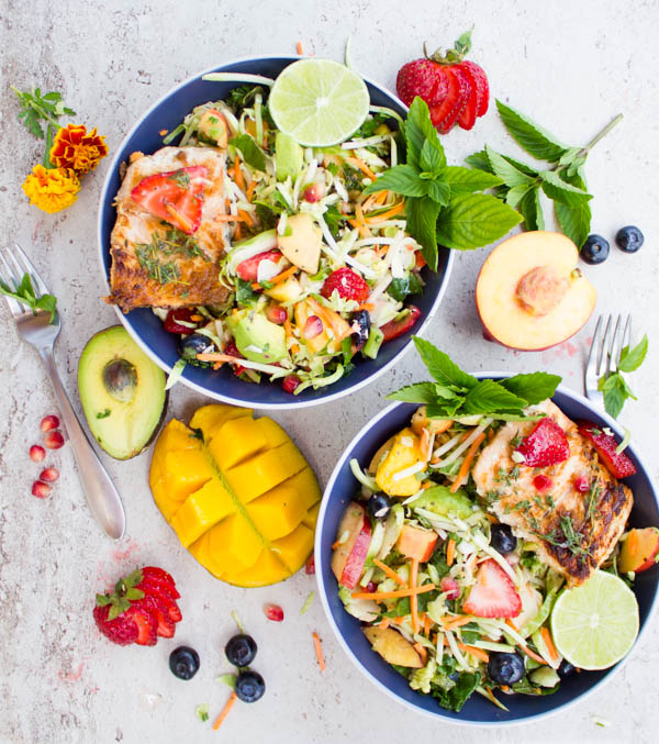 two Grilled Salmon Nourish Bowls surrounded by fresh fruit and mint twigs