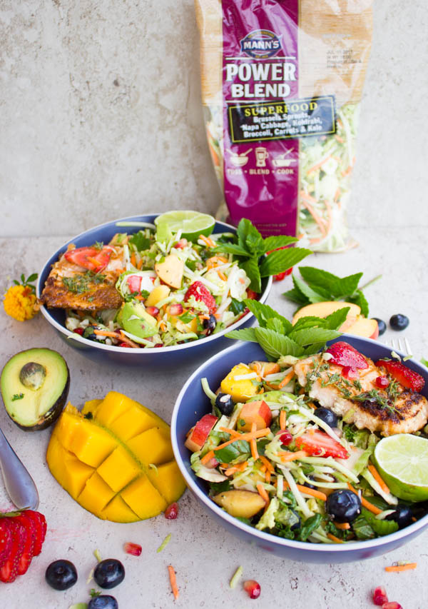 two Grilled Salmon Nourish Bowls with fresh fruit and grated vegetables