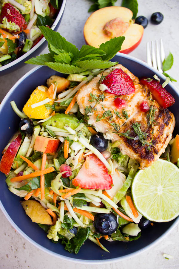 Grilled Salmon Nourish Bowl full of fruit and grated veggies with a piece of grilled salmon on top