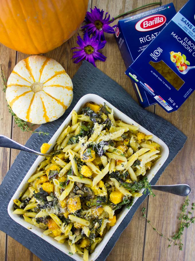 Easy Baked Pasta with Roasted Pumpkin, Kale and Mushrooms in a casserole on a blue place mat with a pumpkin and more pasta in the background