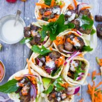 Spicy Harissa lamb shoulder chunks in pita cones with Tahini sauce. A serious Crowd Pleaser that's Loaded with Flavors and a Secret Tip for charring Lamb Chunks I learned form my grandma! Get the recipe and Step by Step at www.twopurplefigs.com