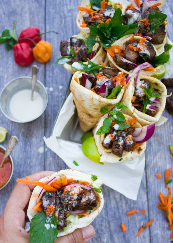 a hand holding a pita cone filled with charred lamb shoulder, grated carrots, fresh herbs and red onion slices with a drizzle of tahini sauce on top.