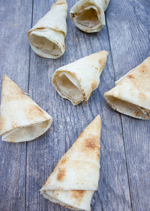 hand-rolled pita cones on a rustic wooden table ready to be filled.