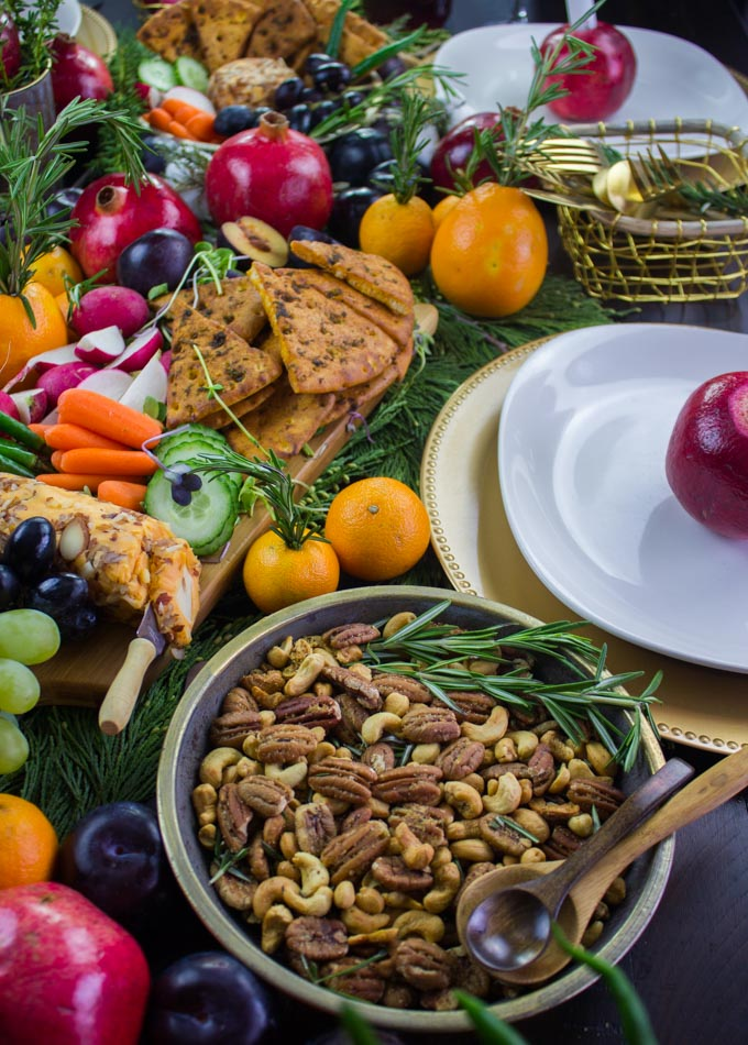 Rosemary Spiced Candied Pecans and Pita Chips arranged on a table with seasonal fruit and plates for a Cheese Party.