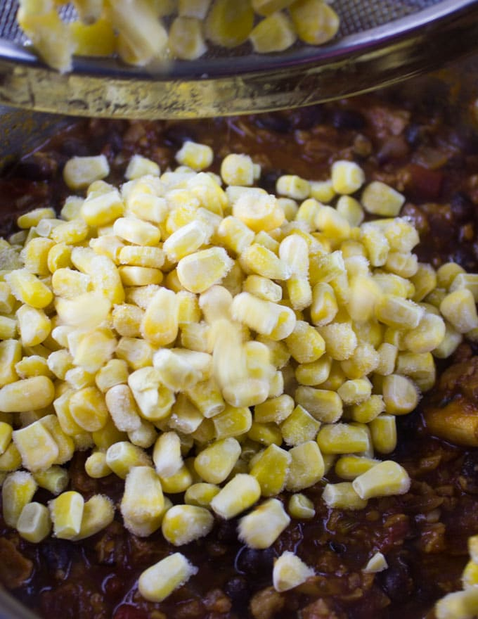 corn being added to a pot of veggie chili