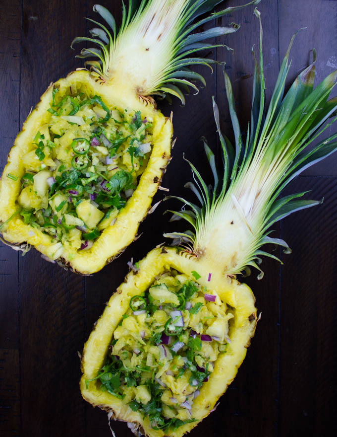 two halved pineapples stuffed with fresh pineapple salsa