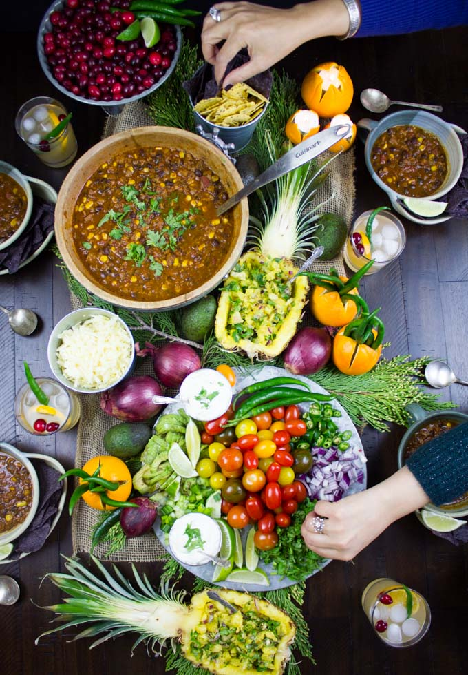 overhead shot of a table with a pot of Vegetarian Chili, filled pineapples and a veggie platter