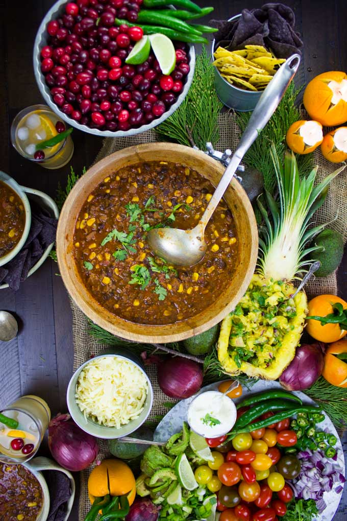 overhead shot of a table with a pot of Vegetarian Chili, a veggie platter, a bowl of cranberries and pineapple salsa