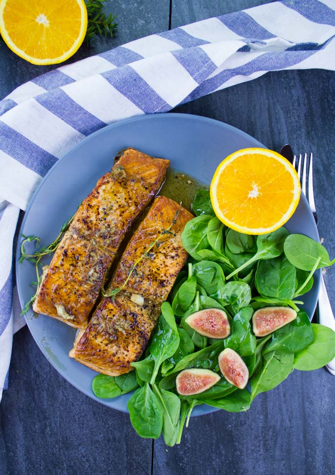 two Garlic Orange Pan-Seared Salmon fillets on a blue plate with a side salad