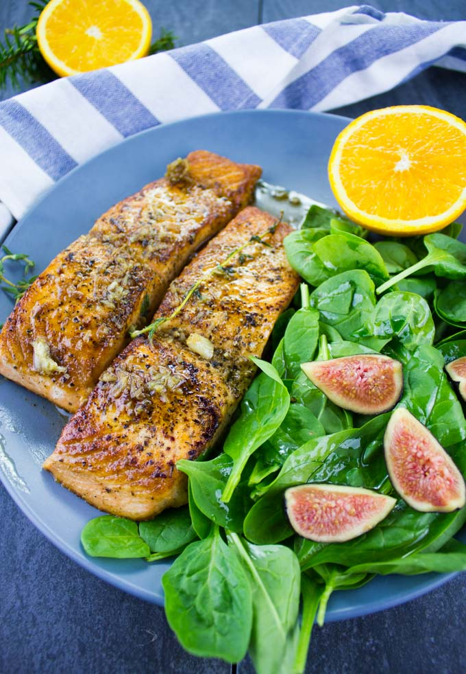 two Garlic Orange Pan-Seared Salmon fillets with a side salad