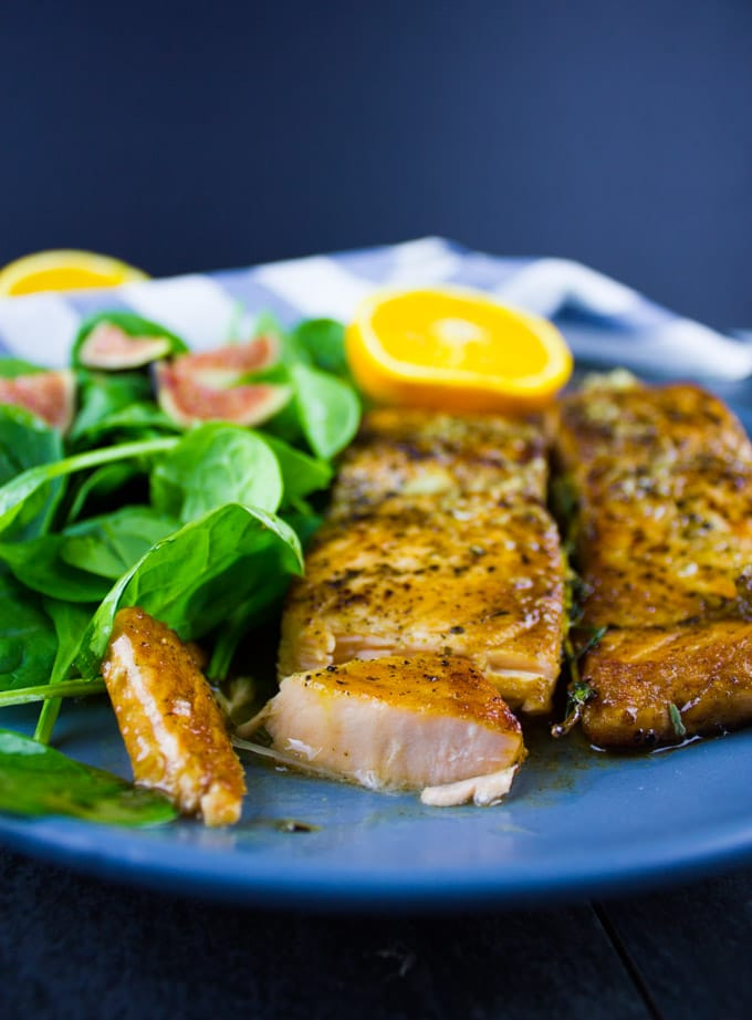 side view of two pan-seared Garlic Orange Salmon fillets on a blue plate with a side salad
